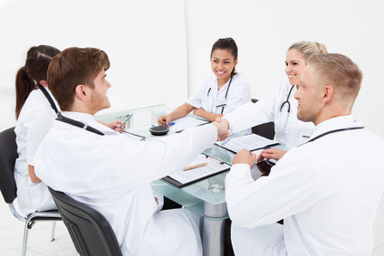Doctors shaking hands at desk in clinic